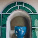 A blue handmade glazed pot in a nook that is framed with green handmade glazed tiles.
