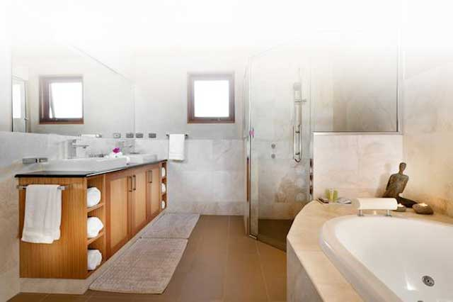A wonderfully bright white tiled bathroom with spa, shower and wooden vanity.