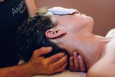 A masseuse holding a woman's neck.
