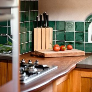 Leela Kitchen with green handmade tiles and wooden chopping boards