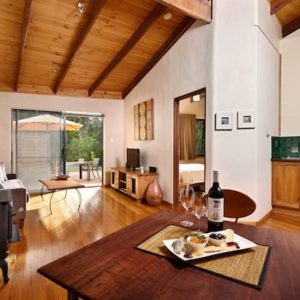 Wooden floor and ceiling and a native Jarrah table in the lounge / dining of Rumi accommodation.