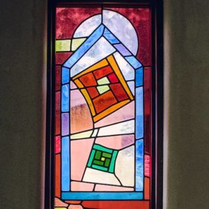 A stain glass window with reds and blues framed in a rendered window.