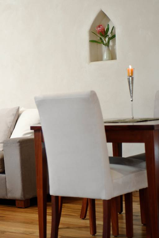 Soft dining chairs with a wooden table and couch in the background