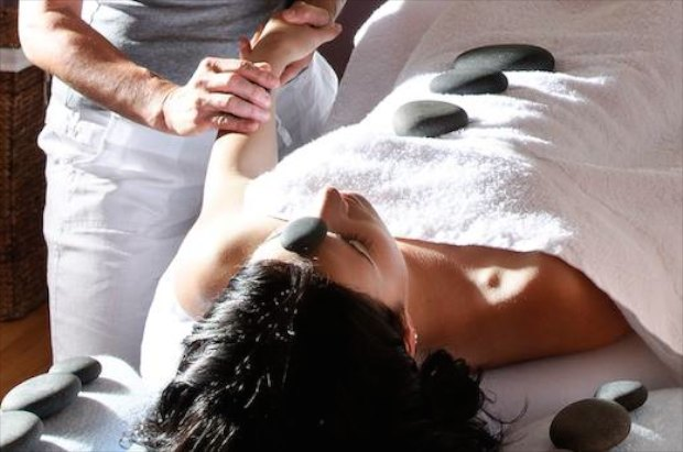 Woman under towels with hot stones on her tummy.