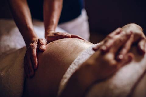 Hands massaging a pregnant belly.