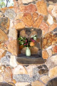 Flowers in a earthenware vase in the alcove of a stone wall.